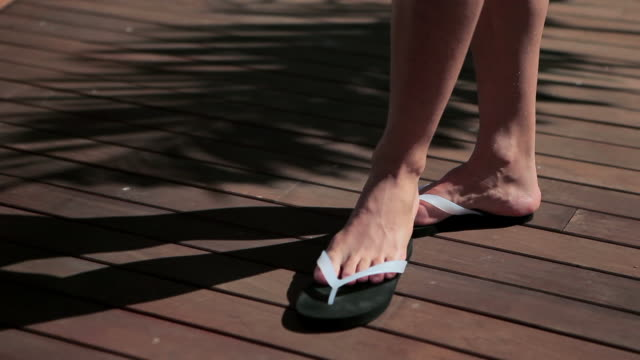 man removing flip flops on decking and lying on sunlounger - sandal stock videos and b-roll footage