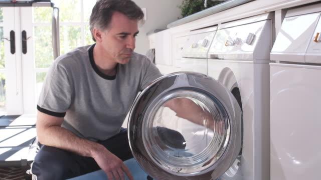MS SHAKY, TU Man removing laundry from washing machine into laundry basket, Phoenix, Arizona, USA