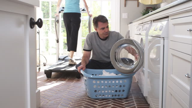 MS TU Man removing laundry from washing machine into laundry basket while woman exercising on treadmill in background, Phoenix, Arizona, USA
