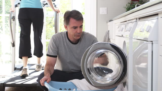 ms man removing laundry from washing machine into laundry basket while woman exercising on treadmill in background, phoenix, arizona, usa - laundry basket stock videos and b-roll footage