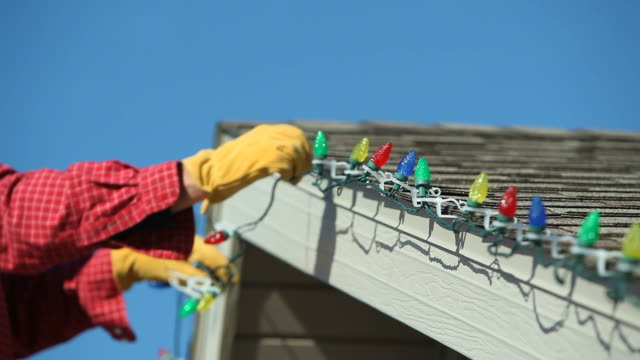 stockvideo's en b-roll-footage met man removing led christmas lights from a house roof - incandescent bulb