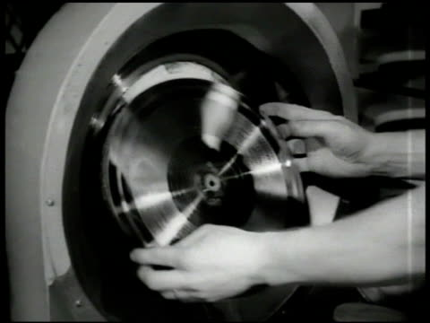 Man removing master music record from machine CU Man removing record MS Woman removing record from machine CU Woman putting record 'biscuit' into...