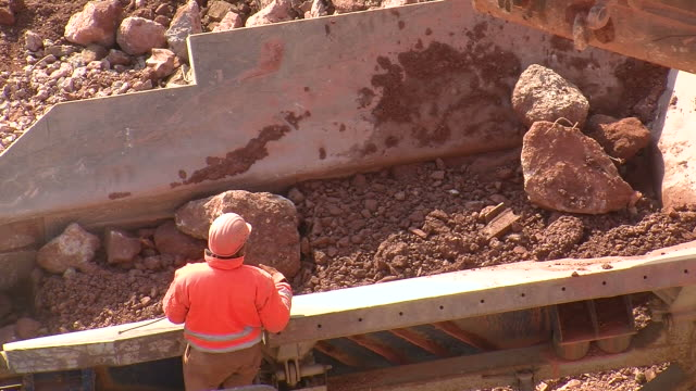 ms man removing metal from chrushing machine at quarry / taben-rodt, rhineland-palatinate, germany - 石切場点の映像素材/bロール