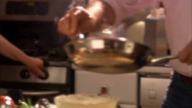 Man removing pan of cooked food from stove range and pouring contents into bowl of beaten eggs