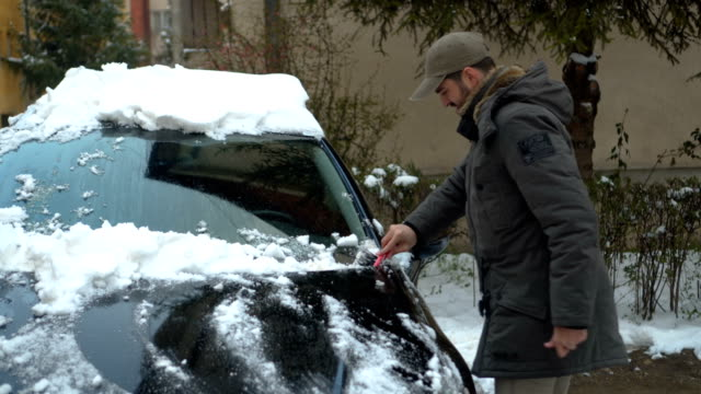 man removing snow from car - absence stock videos & royalty-free footage