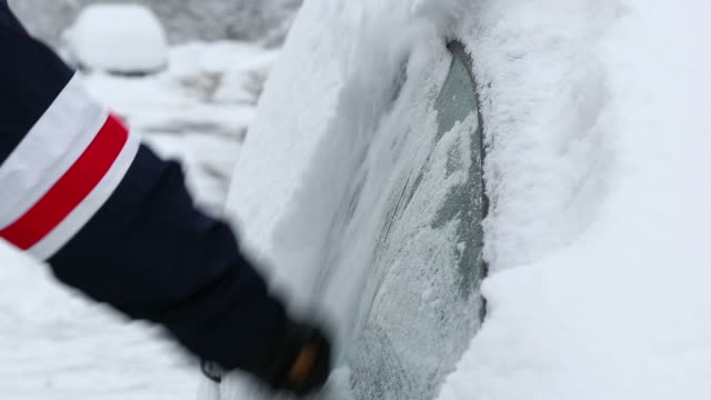 HD: Man removing snow from car window