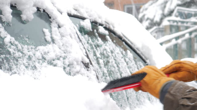 man removing snow from the car after heavy snowfall in winter - heap stock videos & royalty-free footage