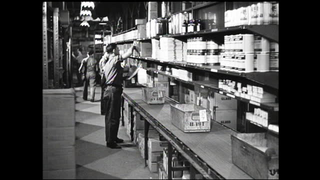 man removing something from safe and closing it; man weighs can on a scale; younger workers collecting items from warehouse shelves and placing them... - 1940 1949 video stock e b–roll