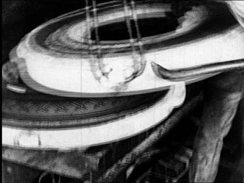 b/w 1925 man removing tire mold to reveal new tire in goodyear tire factory / industrial - 1925 stock videos & royalty-free footage