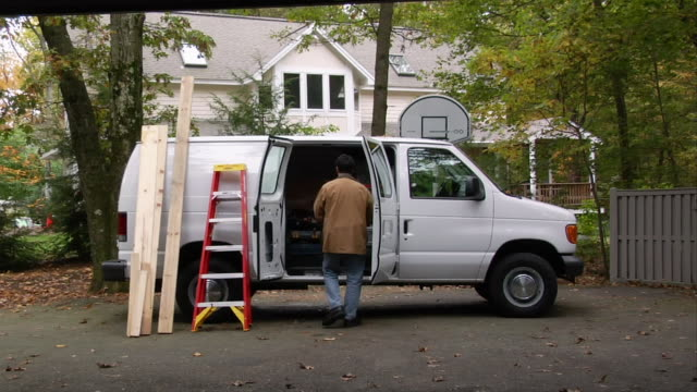 man removing toolbox from van parked in front of suburban house / homeowner approaching and greeting him - toolbox stock videos and b-roll footage