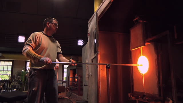 MS PAN Man removing vase from the 2,300 degree reheating oven at glass blowing factory / Windsor, Vermont, USA
