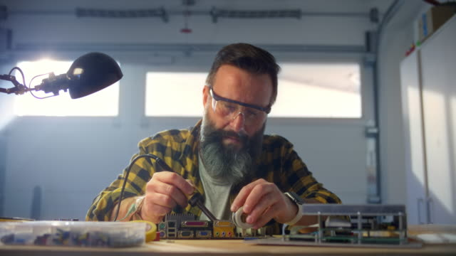 slo mo man repairing a circuit board by soldering it in his workshop - table top shot video stock e b–roll