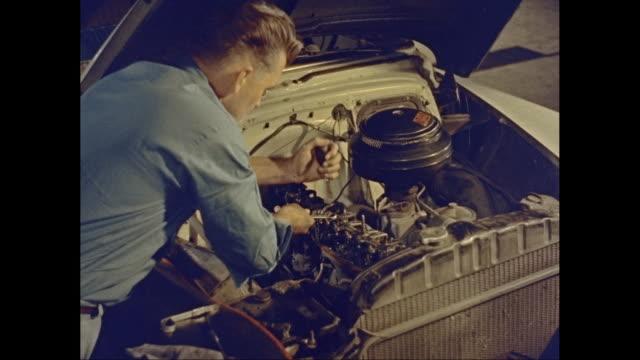 CU Man repairing car engine in garage / United States