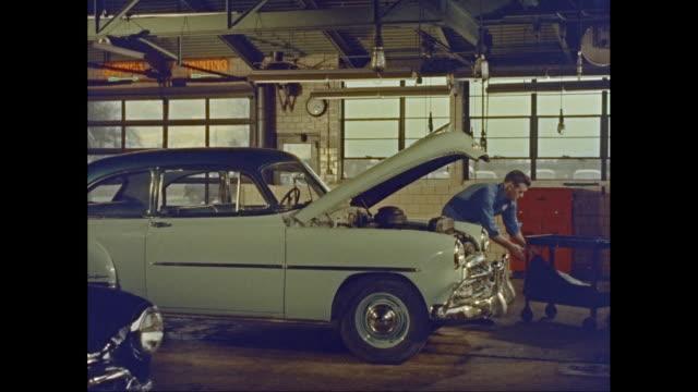 MS Man repairing car in garage / United States