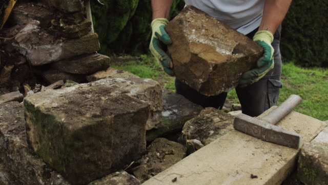 man repairing dry stone wall - stone material stock videos and b-roll footage