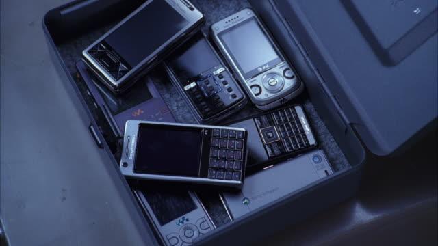 vidéos et rushes de a man repeatedly places a cell phone in a security box. - jetée