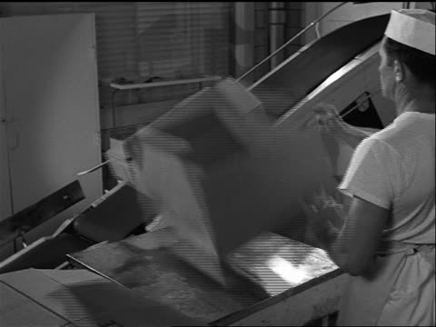 stockvideo's en b-roll-footage met b/w 1957 man repeatedly putting bread into boxes + onto conveyor belt in factory/bakery - 1957