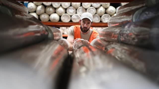 倉庫内の棚の上のカーペットを重ね交換男 - ラグ点の映像素材/bロール