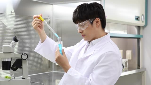 vídeos de stock, filmes e b-roll de a man researcher doing experiment in the lab - amostra científica