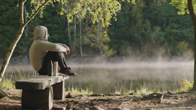 a man resting after his morning exercise out by the lake - park bench stock videos & royalty-free footage