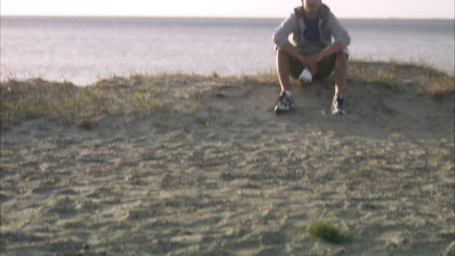 a man resting after jogging on the beach malmo sweden. - ein mann allein stock-videos und b-roll-filmmaterial