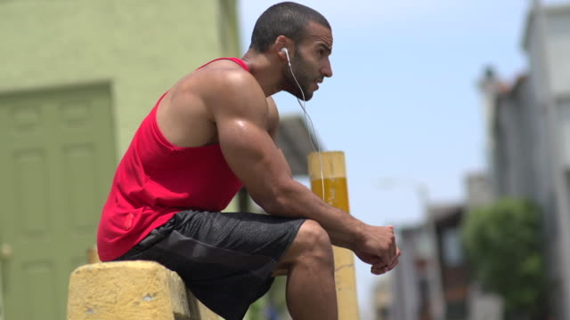 A man resting after working out in a urban alley.  - Slow Motion