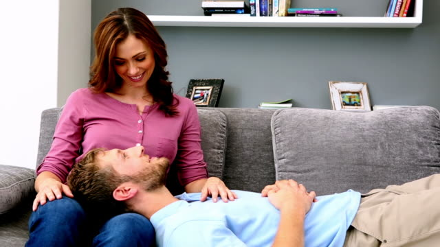 Man resting head on partners lap and chatting