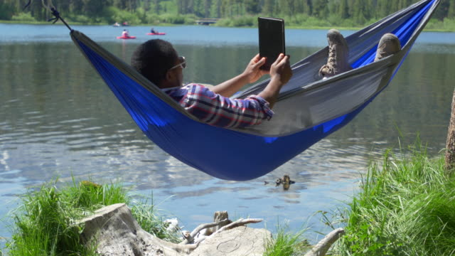 a man resting in a hammock and using a tablet mobile device near a mountain lake. - プレイドシャツ点の映像素材/bロール