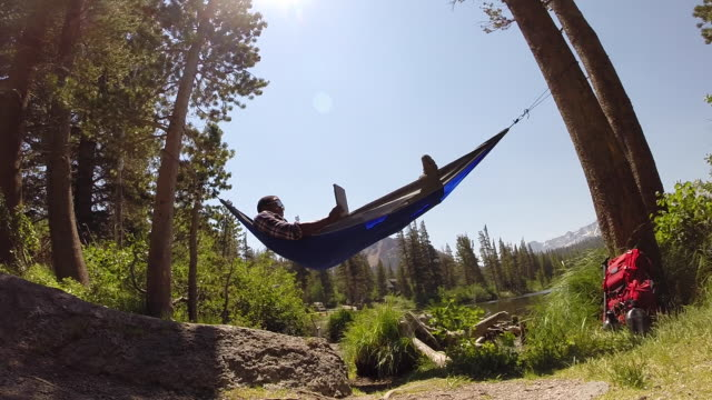 vídeos de stock, filmes e b-roll de a man resting in a hammock and using a tablet mobile device near a mountain lake. - rede de dormir