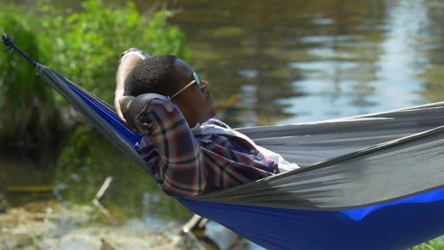 A man resting in a hammock near a mountain lake. - Slow Motion