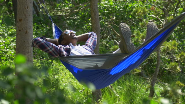 A man resting in a hammock near a mountain lake.