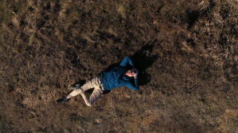 vídeos y material grabado en eventos de stock de hombre descansando en el campo - acostado