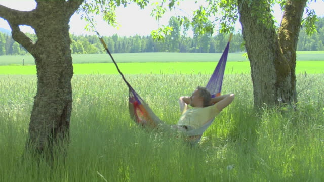 stockvideo's en b-roll-footage met man resting in hammock, peace of mind - formele tuin