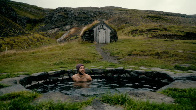 stockvideo's en b-roll-footage met man rust in hete natuurlijke zwembad in ijsland - warmwaterbron