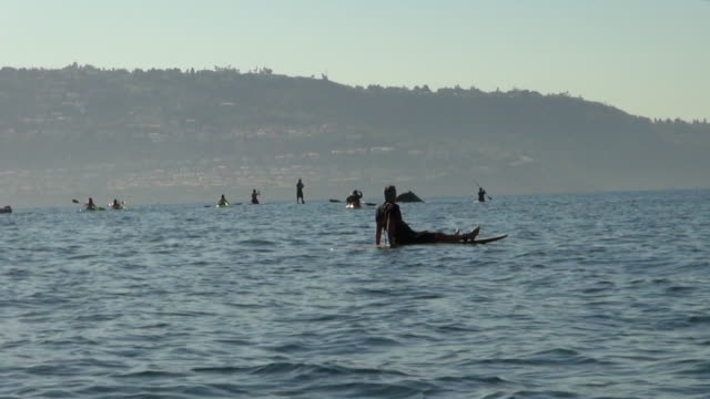 man resting in paddleboard while watching the whale - whale watching stock videos and b-roll footage