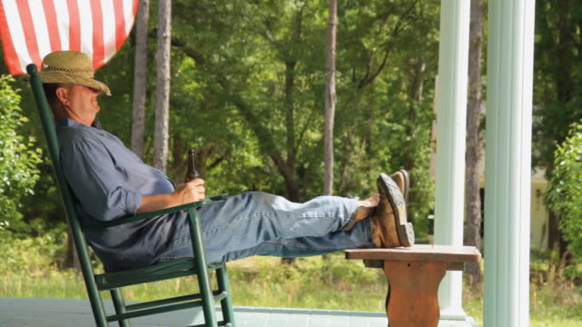 WS Man resting in porch on rocking chair with beer bottle, American flag in background / Madison, Florida, USA