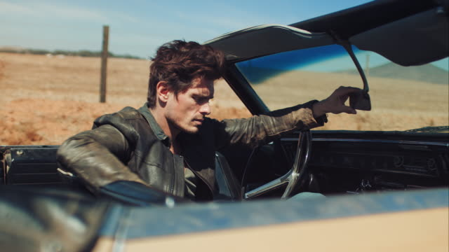 man resting in retro car on dirt road - man convertible stock videos & royalty-free footage