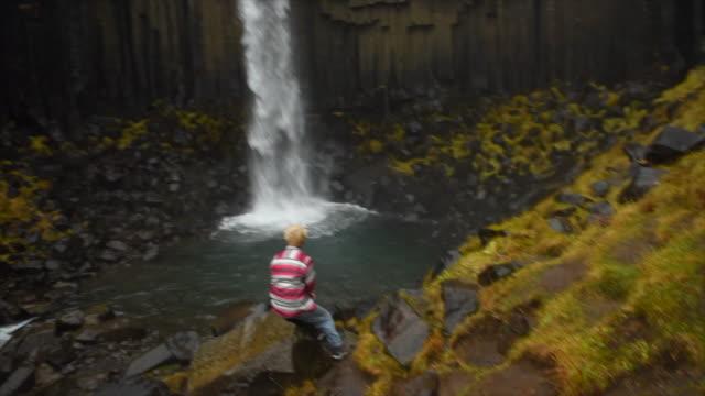A man resting near Svartifoss Waterfall in Skaftafell in Vatnajokull National Park river flowing in Iceland, Europe. - Slow Motion