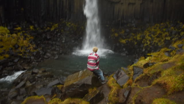 a man resting near svartifoss waterfall in skaftafell in vatnajokull national park river flowing in iceland, europe. - slow motion - goodsportvideo stock videos and b-roll footage