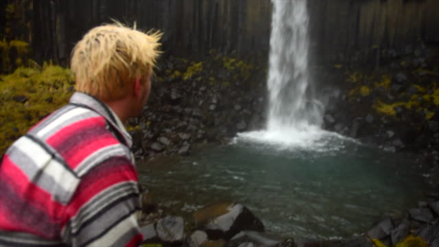 A man resting near Svartifoss Waterfall in Skaftafell in Vatnajokull National Park river flowing in Iceland, Europe. - Slow Motion