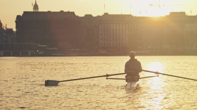man resting on rowboat in river at sunset - sculling video stock e b–roll
