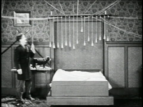 vídeos de stock, filmes e b-roll de b/w 1923 man (snub pollard) retracting murphy bed / it reveals burning fireplace / short - 1923