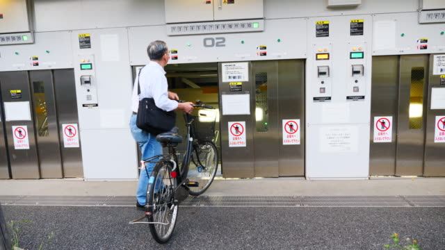 vidéos et rushes de a man retrieves his bike from automated parking in tokyo - se garer
