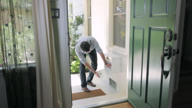 MS Man retrieving mail from mailbox and entering in house / Santa Monica, CA, United States