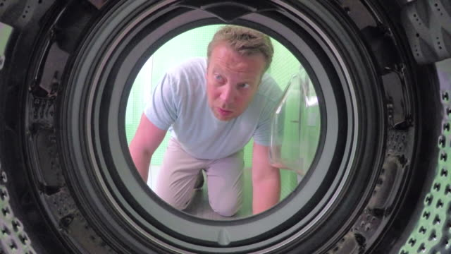 pov of man retrieving sock from washing machine - cercare video stock e b–roll