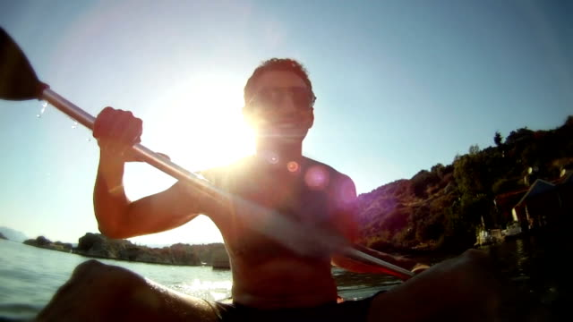 Man rhythmically kayaking into the sun