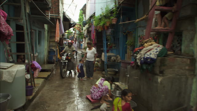 vidéos et rushes de a man rides a bicycle through a small alley in mumbai, india. available in hd. - bidonville