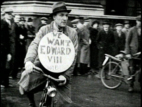 a man rides a bicycle while wearing a sign which proclaims we want edward viii - anno 1936 video stock e b–roll