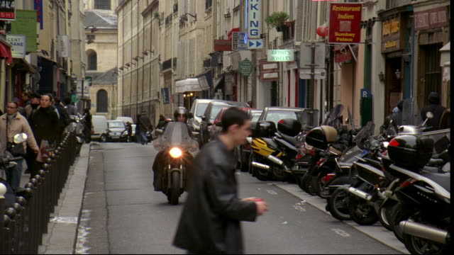 A man rides a motorcycle down a narrow street in Paris, France.