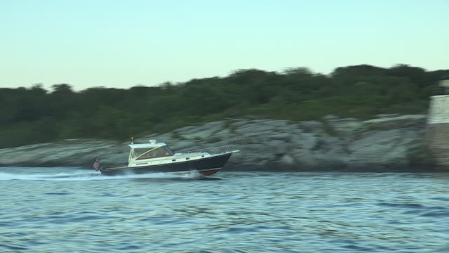 a man rides a powerboat past newport's castle hill lighthouse. - hill点の映像素材/bロール